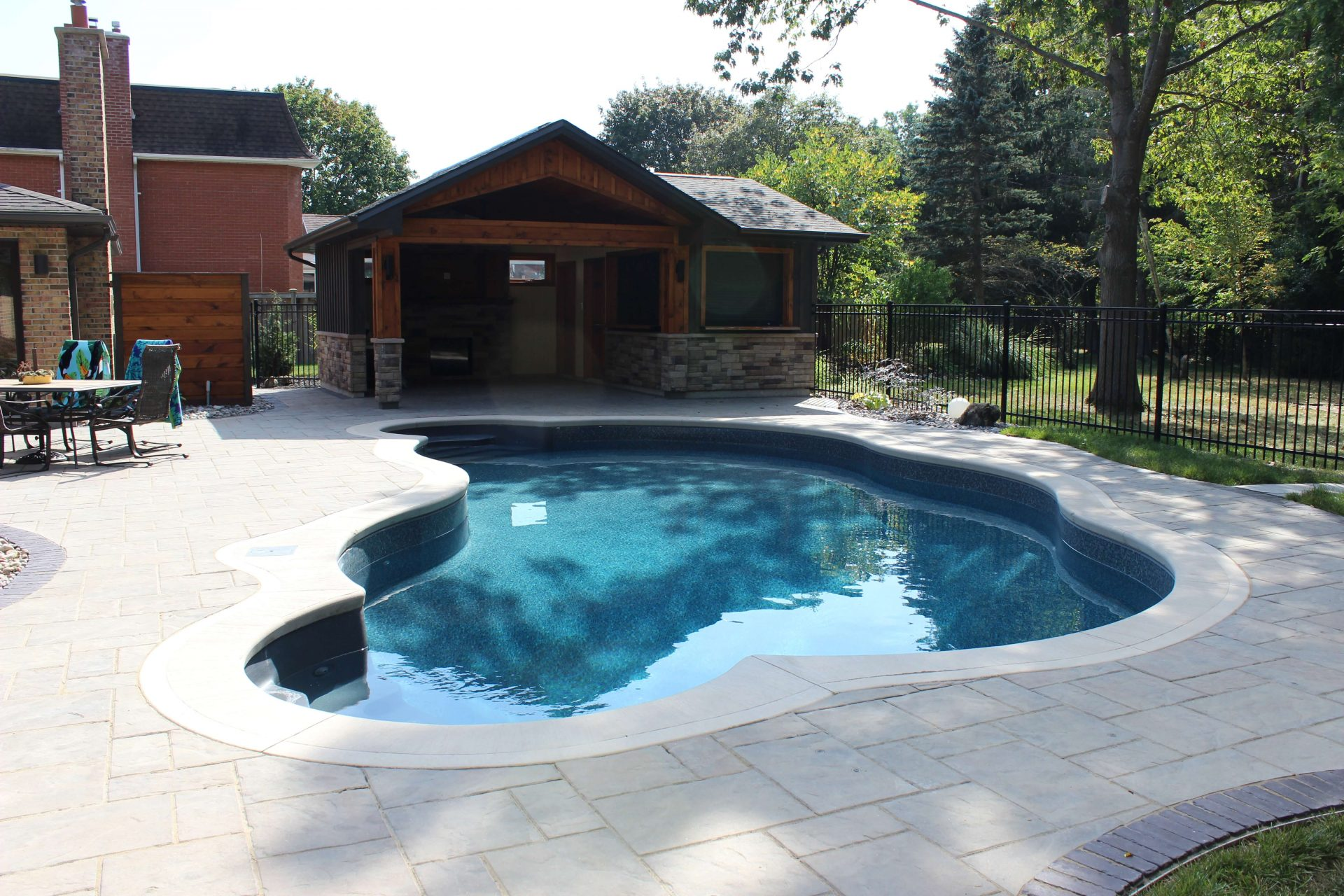 Modern pool house in front of small underground pool