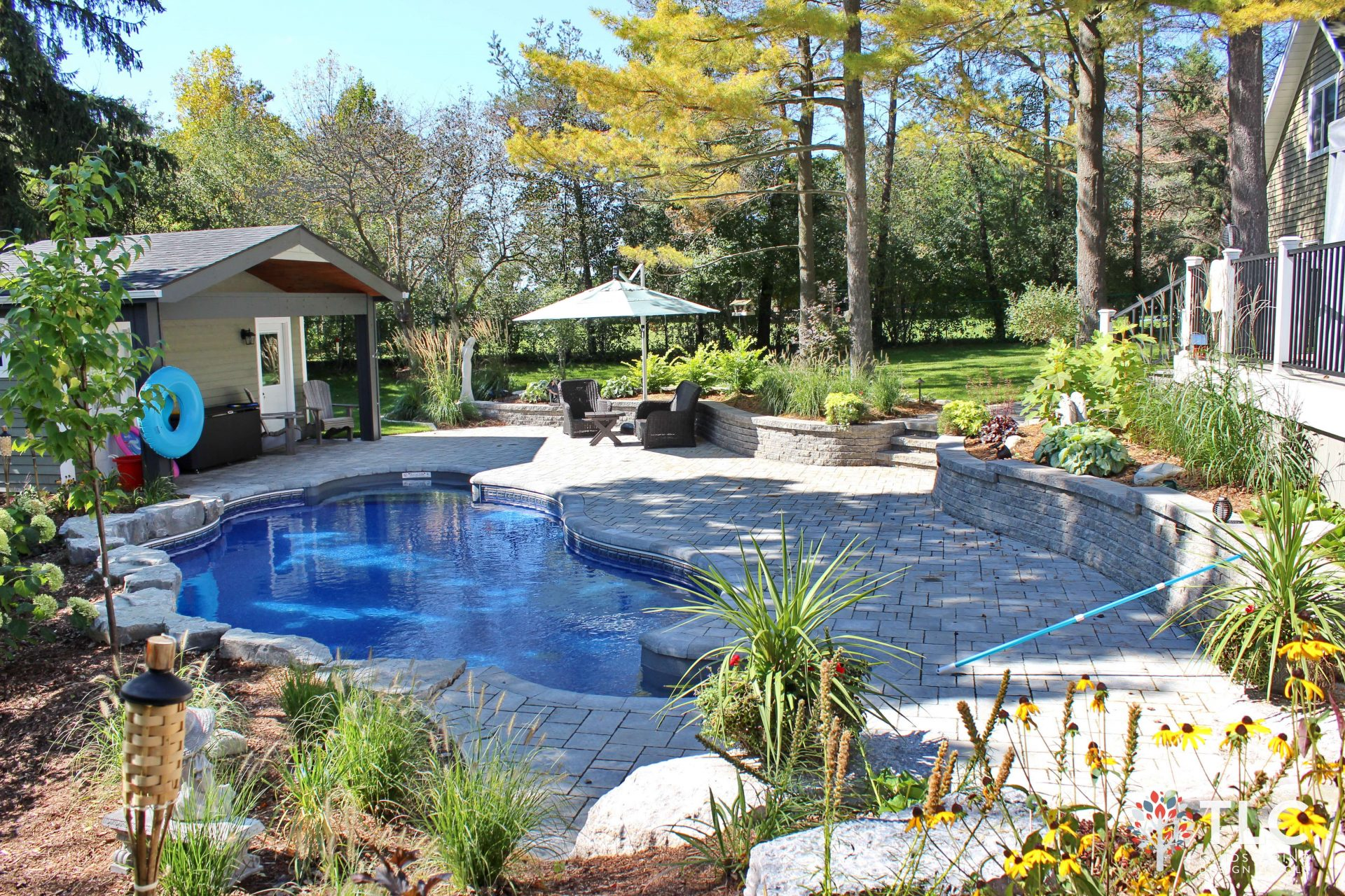 Side view of backyard featuring pool, lounge area and pool house