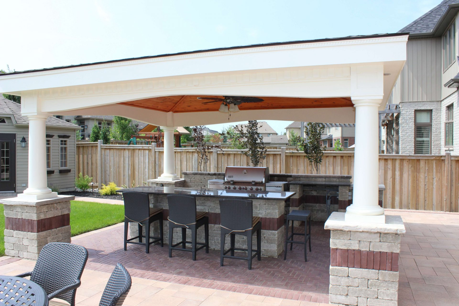 Covered open concept backyard entertainment area with barbeque