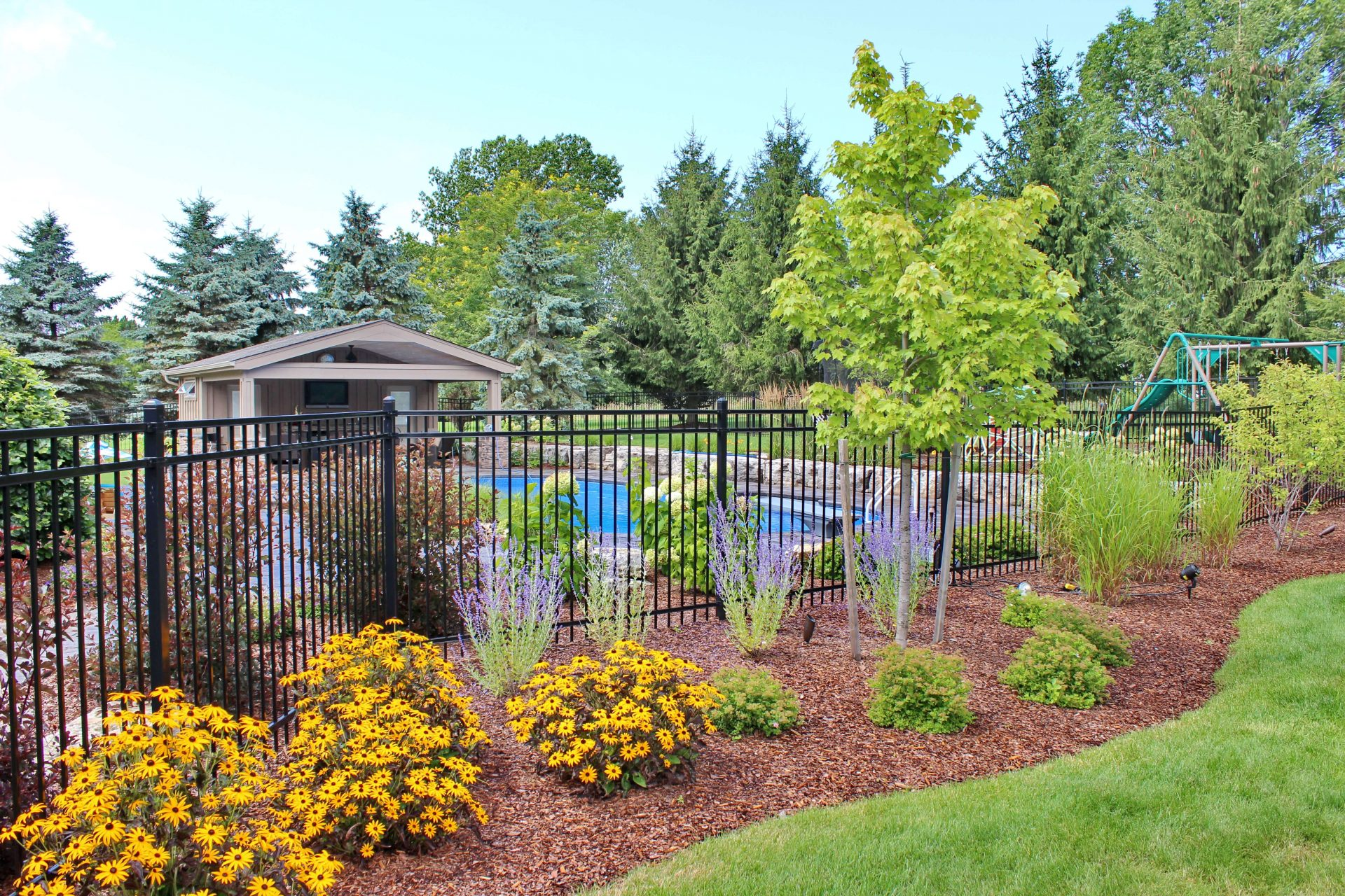 Large backyard separated by iron fence overlooking underground swimming pool and swing set