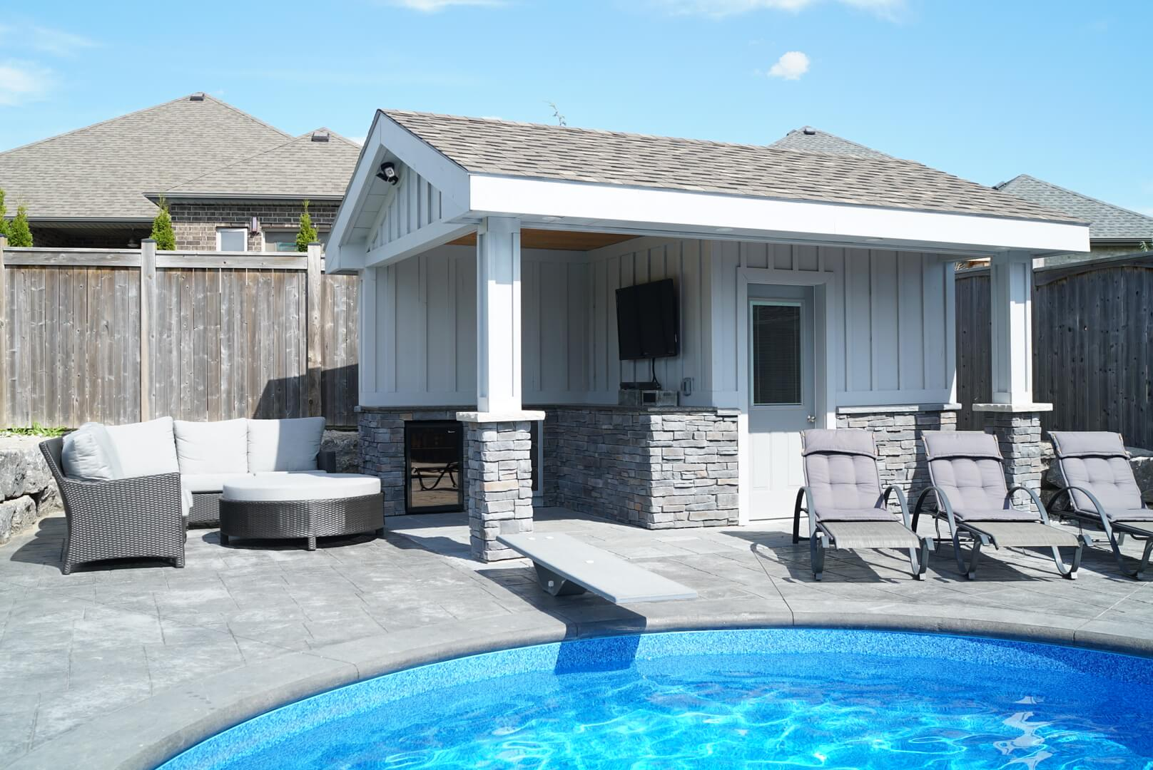 Small pool house behind pool of backyard
