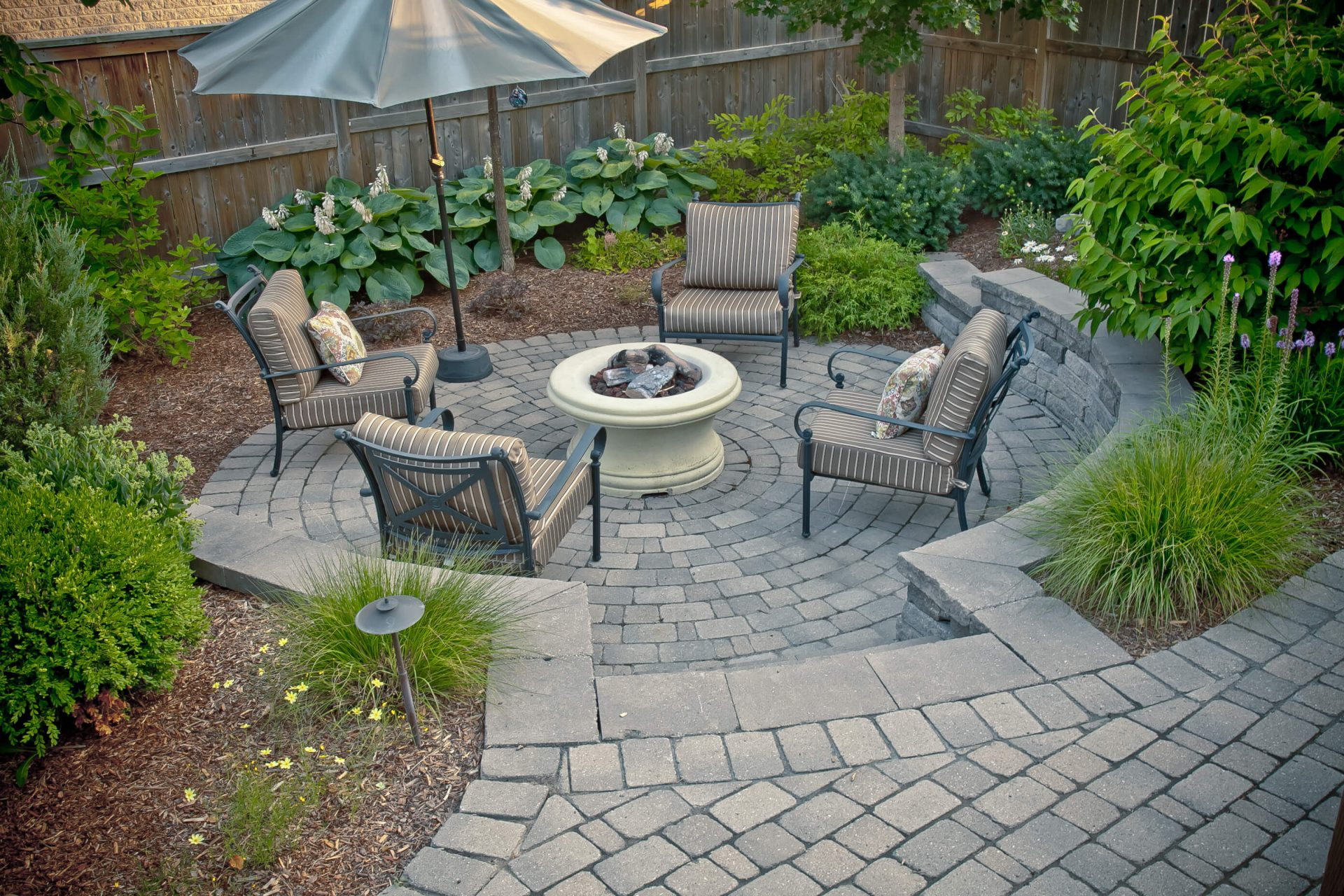 Lounge and fire pit area on cobble stoned path surrounded by garden
