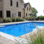 Diving board featured over top beautiful underground swimming pool in backyard