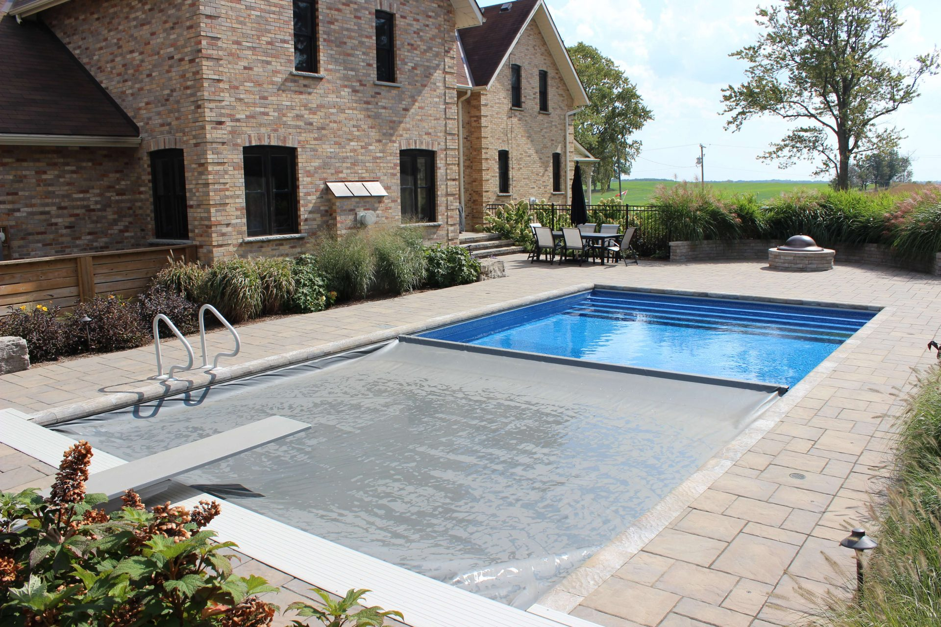 Underground pool featured in backyard of large home in the country