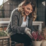 How to Extend the Gardening Season- woman seeding plants in three pots with colourful, small plants
