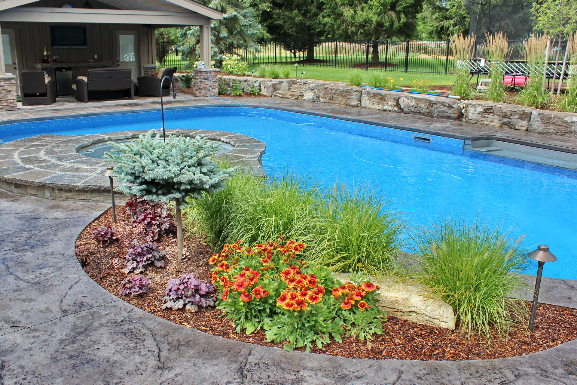 Beautiful pool with natural stone look, pool house, pergola, stone wall and in-ground hot tub by TLC Landscaping