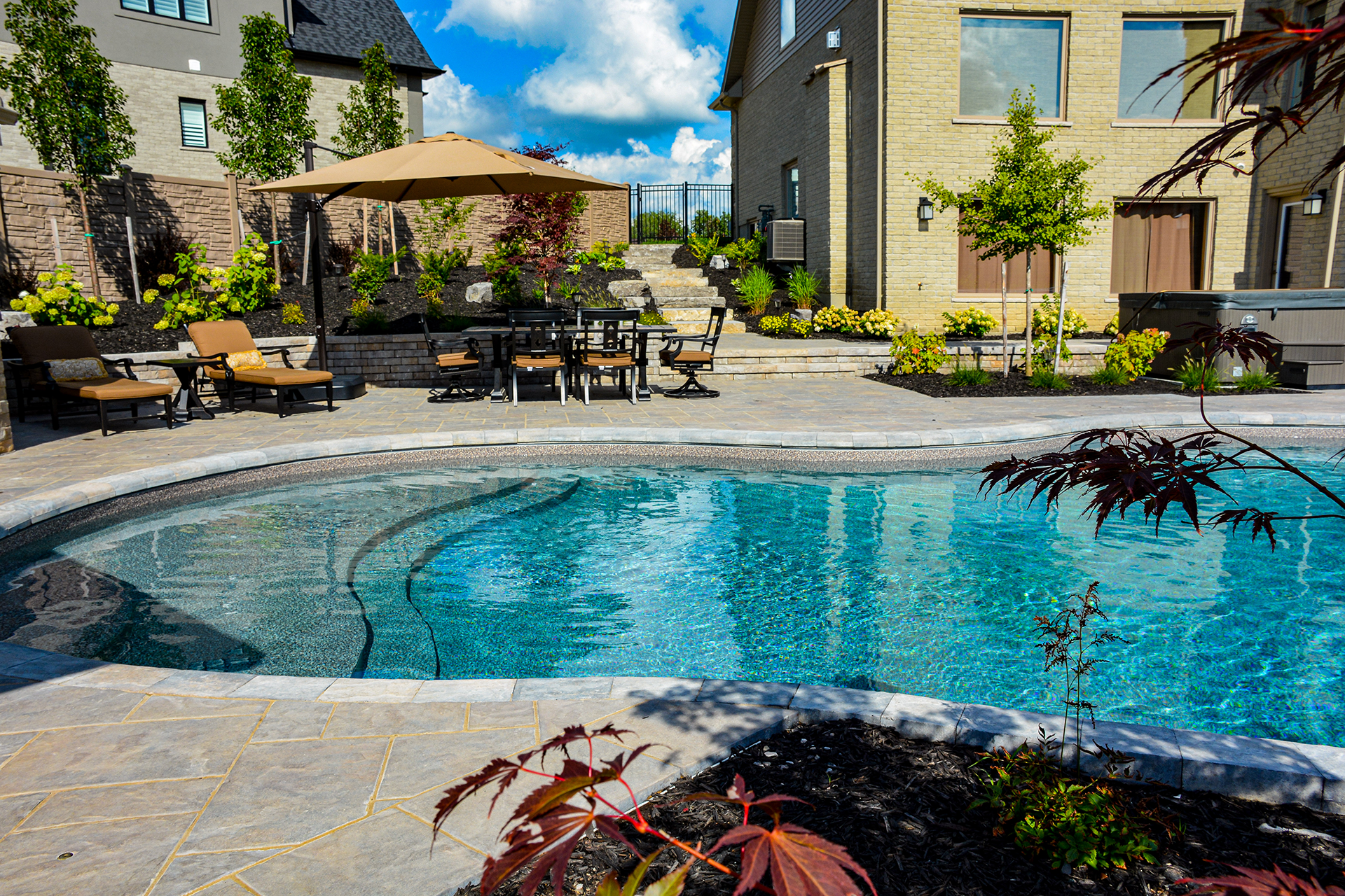 A glamour shot of a beautiful backyard pool and outdoor living space