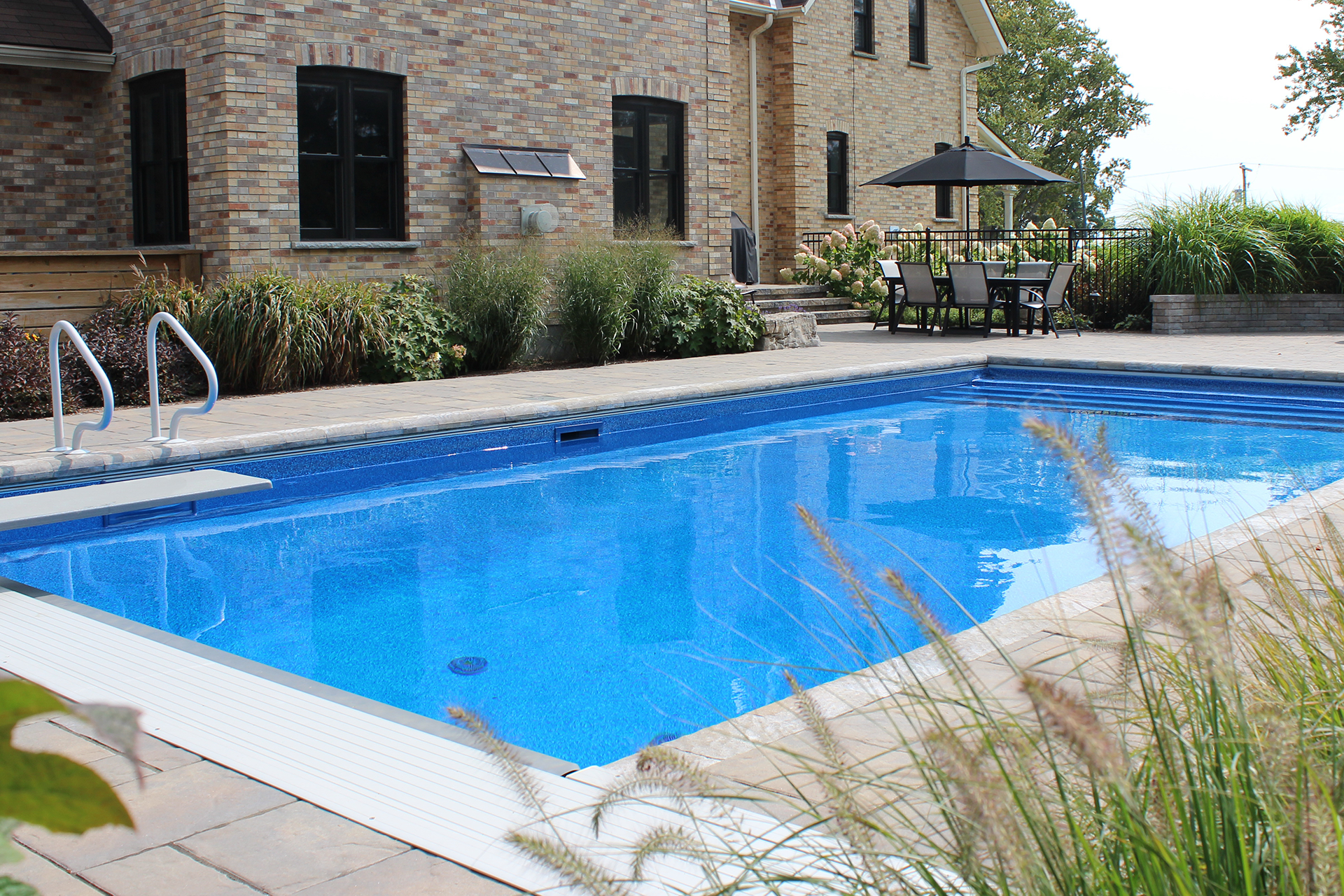 A unique backyard pool and pool patio/deck by TLC Landscaping