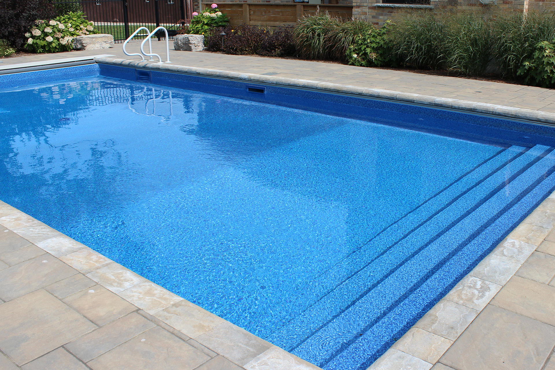 A calm pool with clean and vibrant blue liner by TLC Landscaping