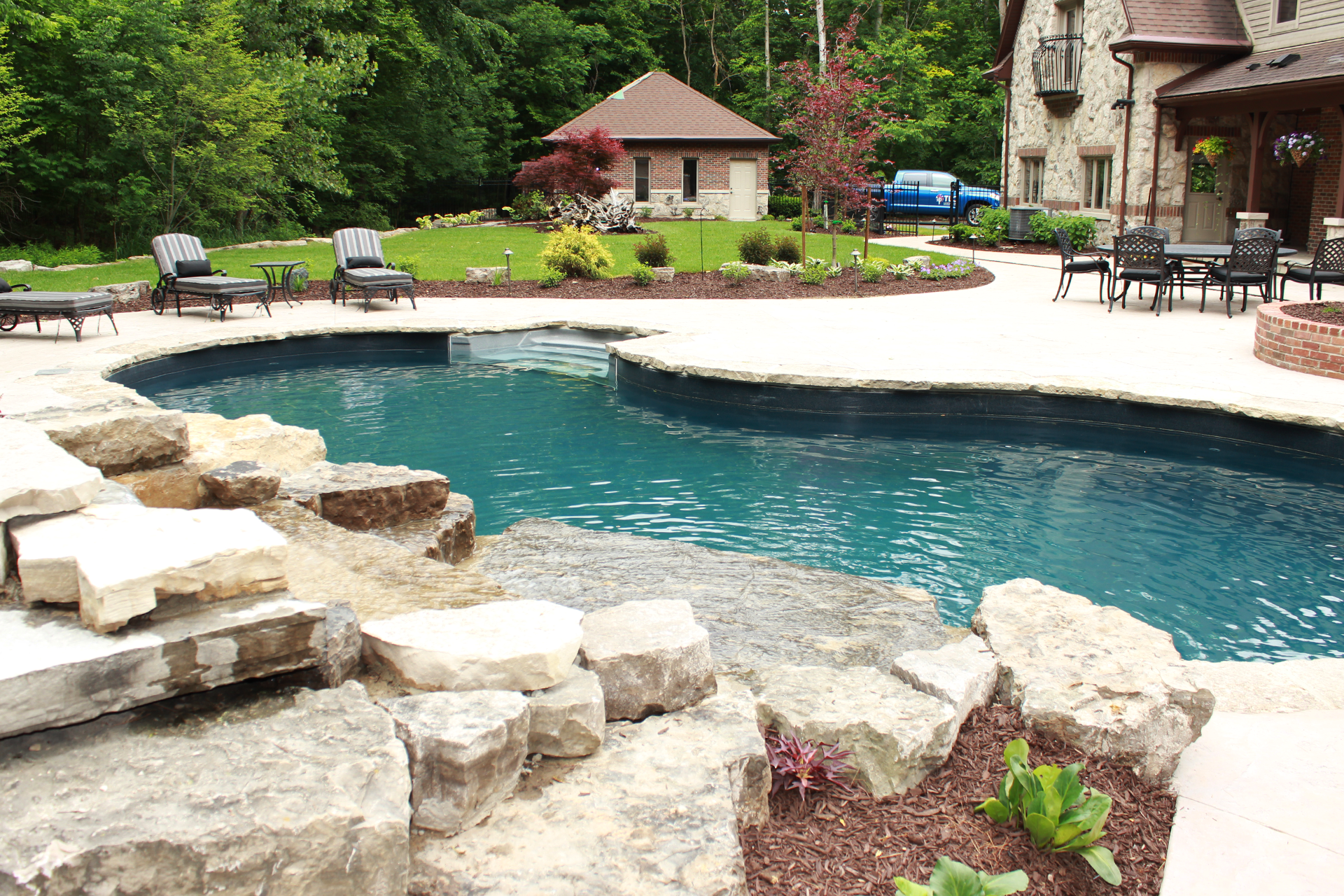 A pool in a natural setting by TLC Landscaping using natural stone with water feature