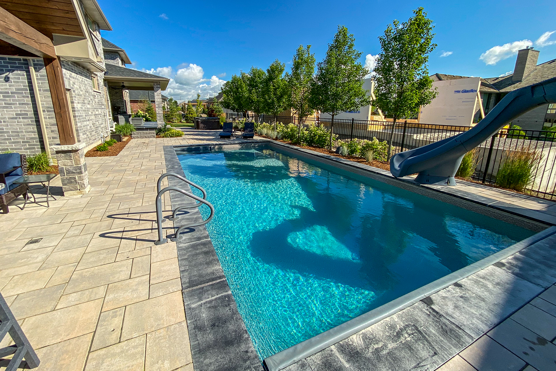 Backyard outdoor living space with a pool, roofed bar and pool slide by TLC Landscaping