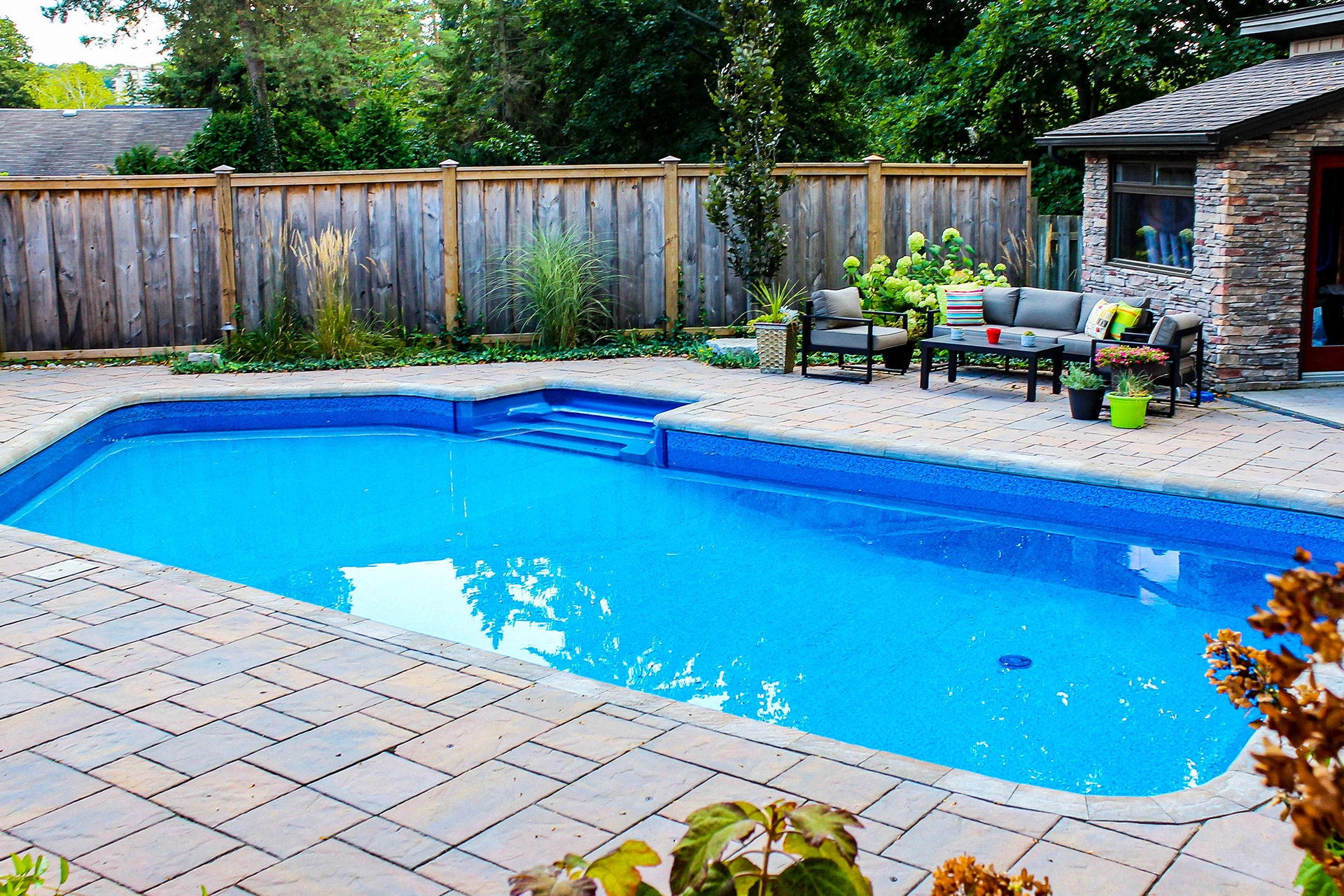Image of an impressive backyard pool, pooldeck and pool house by TLC Landscaping